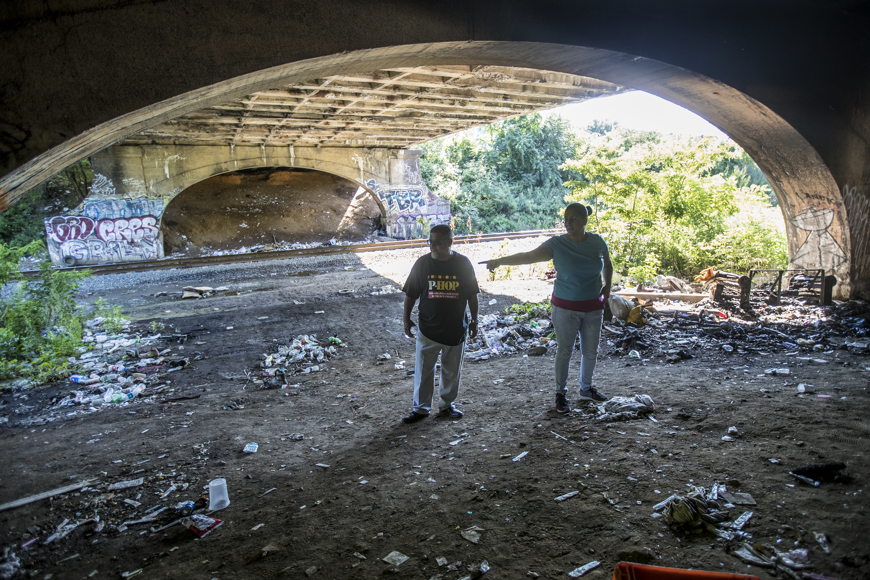 Charito Morales, right, points out to Sam Tiru, left, of the Public health Management Corporation, where a a family was living under the A Street bridge until recently.