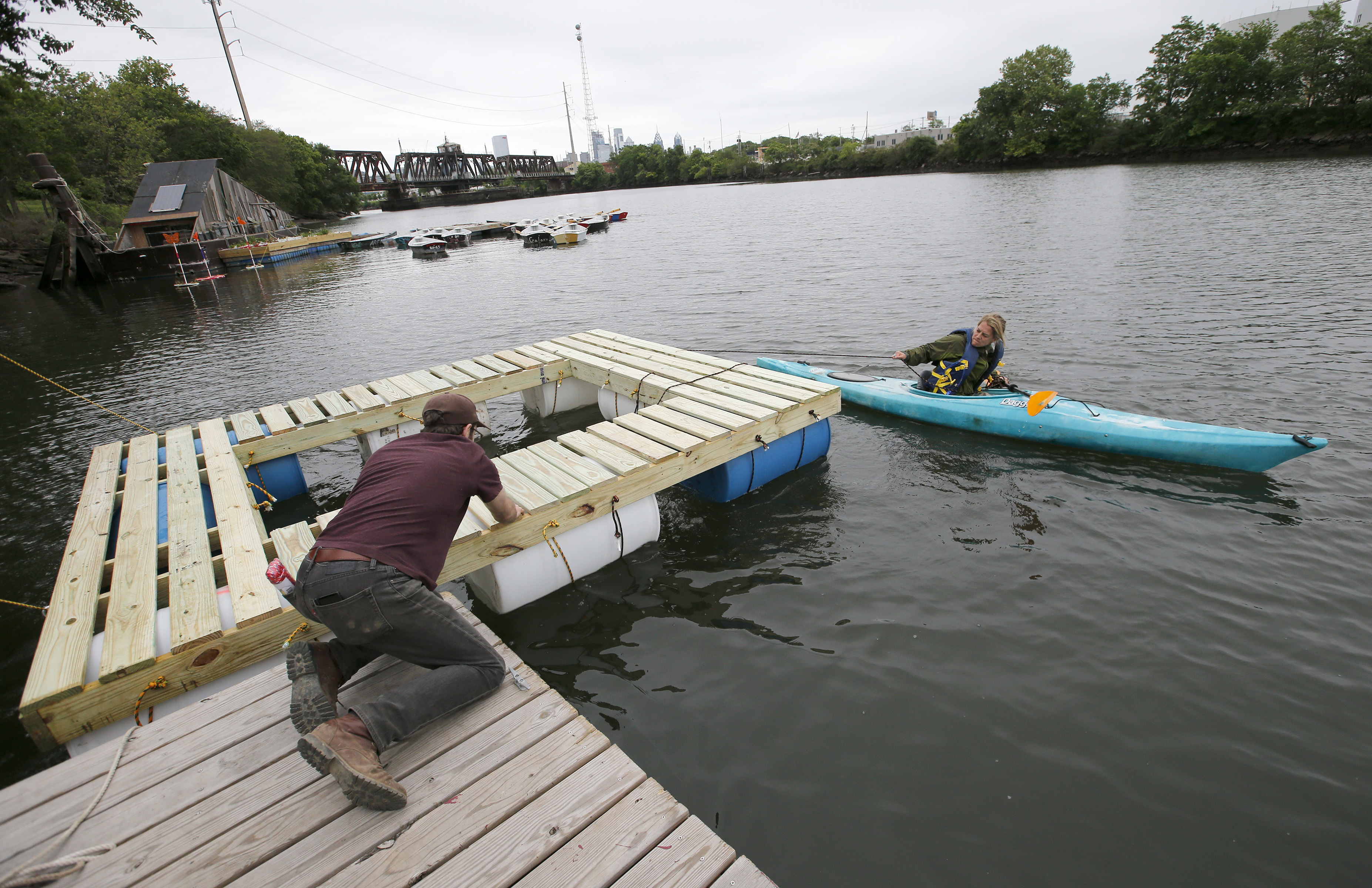 Bethany Wiggin (on the kayak) helps Jacob Rivkin place the Bio Pool in the Schuylkill River at the Bartram's Garden Community Boathouse. The University of Pennsylvania Program in the Environmental Humanities launched a biochar-based floating filter to clean the river. YONG KIM / Staff Photographer