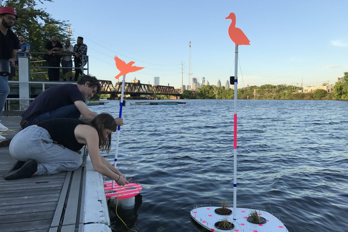 Gabriel Kaprielian, a professor in the architecture department at Temple University's Tyler School of Art, drops his floating habitat pods into the Schuylkill River at Bartram's Garden with help from Kya Kerner, a recent Tyler graduate. It is part of Ecotopian Toolkit for Wetland, a design competition meant to stoke interest in the river and engagement in the environmental challenges ahead.