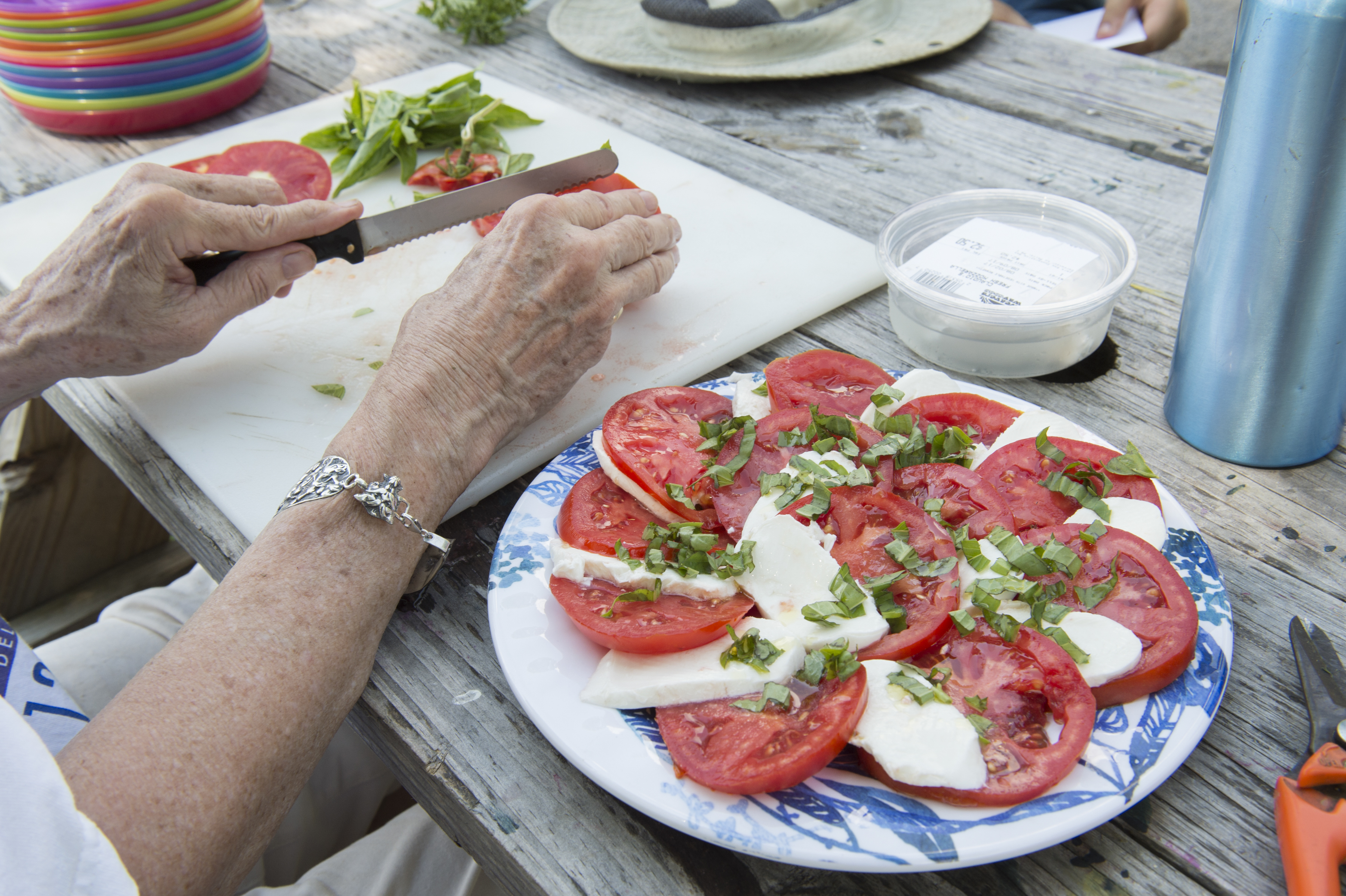 Margaret Guthrie, a Hope Farm volunteer cuts tomatoes for a tomato, basil and mozzarella salad at Hope Farm in Philadelphia. (Jonathan Wilson / For the Inquirer)