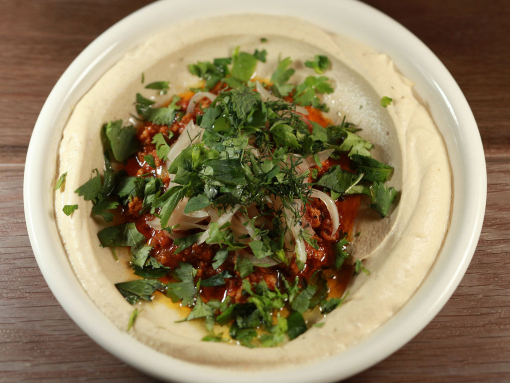 Persian lamb hummus at Dizengoff (top), one day with pickles, another stewed with orange and pistachios, hits with an aromatic Persian spice. (DAVID M WARREN / Staff Photographer)