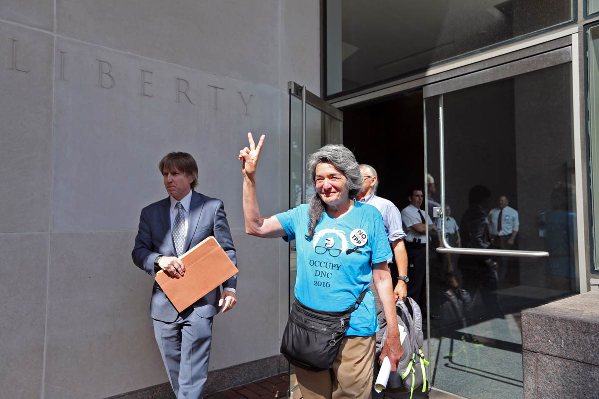Anna Marie Stenberg, 69, gives a peace sign after being released from federal court Wednesday, July 27, 2016, after being arrested Tuesday night for climbing a security fence during the DNC.