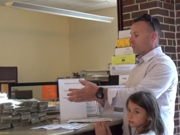 Rob Fernandes, father of three, gestures toward the 7,143 dollar bills he used to pay his school taxes in Fork Township, Pa., on Aug.. 27, 2013. The scene is taken from his YouTube video.