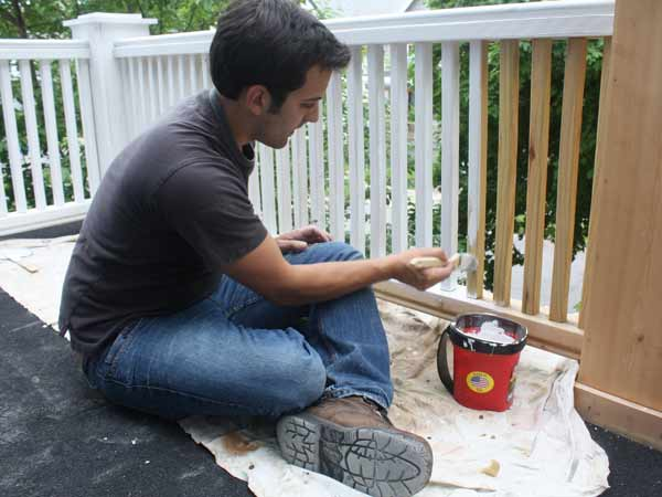 Mike Puma, 24, paints the porch railing of his Buffalo, N.Y. home June 4, 2014. Puma bought his home for $1 in February and is slowly making it habitable. It's taken a lot of time and money to rehab the 99-year-old home, but he wanted to save it from demolition. (Alana Semuels/Los Angeles Times/MCT)