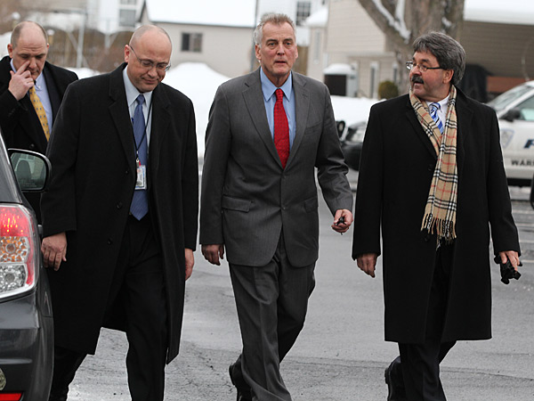 Don Tollefson, second from right, walks with his lawyer, Michael McGovern, right, as he turns himself in to Warminster plice on Tuesday February 18, 2014. He faces felony charges for felony charges for allegedly scamming dozens of people out of more than $100,000 meant to go to charitable organizations, according to the Bucks County District Attorney´s Office. ( MICHAEL BRYANT / Staff Photographer )
