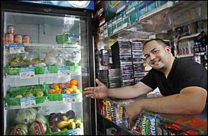 Jose Nunez of Robles Grocery recently qualified for a free refrigerator that allows him to sell yogurt, fruit salad and other perishables.<br />(Alejandro A. Alvarez / Staff Photographer)
