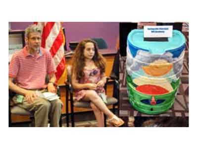 Conference attendee Alison sits beside her hand-painted rain barrel. (Photo courtesy ECA)