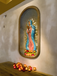 A wooden statue of Our Lady of Guadalupe stands in a metal bathtub at El Camino Real.