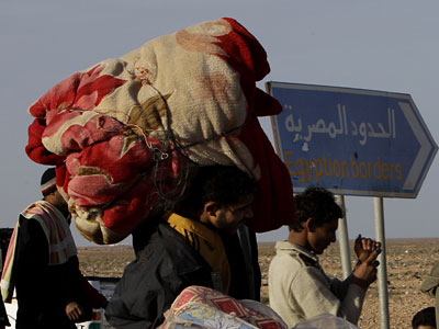 An Egyptian man who fled from Libya through the Salloum land port gate carries his belongings at the Egyptian-Libyan border, in Salloum, Egypt. (Hussein Malla / AP Photo)