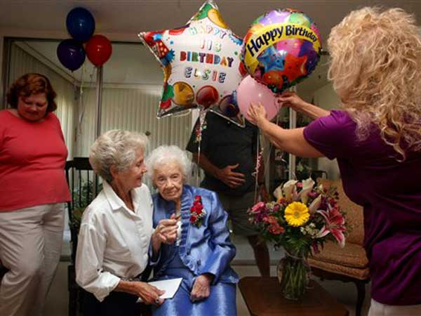 FILE - In an April 5, 2012 file photo Elsie Thompson, center, is surrounded by her caretakers Arleen Pensinger, left, and Susie Harper, right, while visiting with neighbor Maryann White during Thompson´s 113th birthday. Thompson, the oldest person in the United States died March 21, 2013. (AP Photo)
