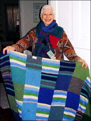 Esther wearing a thrift-store sweater and one of her neck scarves holding a sweater quilt.