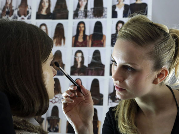 A model has make-up applied backstage before the BCBG Max Azria Fall 2013 collection is modeled during Fashion Week in New York,  Thursday, Feb. 7, 2013. (AP Photo/Richard Drew)