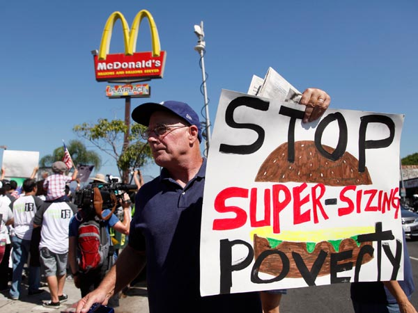 Kevin Cole protests outside a fast food restaurant on Thursday Aug. 29, 2013 in Los Angeles. Fast-food protests were under way Thursday in U.S. cities including New York, Chicago and Detroit, with organizers expecting the biggest national walkouts yet in a demand for higher wages. (AP Photo/Nick Ut)