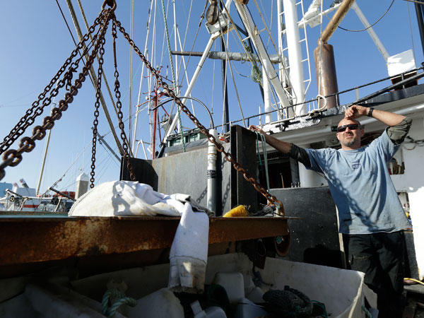 """Steve Fitz, owner of the fishing boat Mr. Morgan, is interviewed on his boat docked in Half Moon Bay, Calif., Tuesday, Feb. 12, 2013. Fleets of unused, weathered fishing boats, shuttered processing businesses and idle fishermen have been the image of California´s once-thriving fishing towns over the past decade. But two years ago federal regulators decided to implement strict """"catch shares,"""" or fishing quotas, along the Pacific Coast after seeing the management technique help fisheries rebound in other places. (AP Photo/Jeff Chiu)"""
