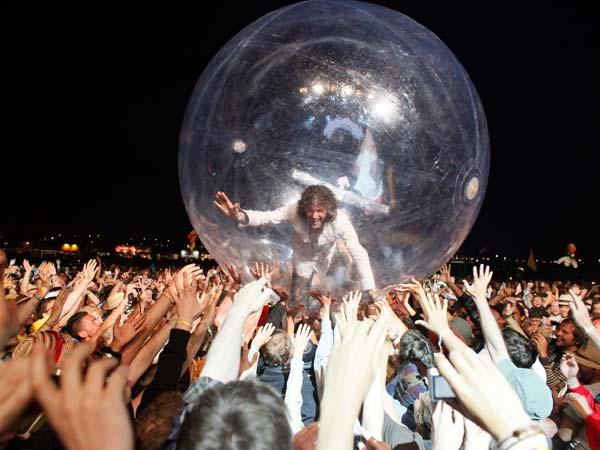 U.S. band The Flaming Lips frontman Wayne Coyne takes a trip across the heads of the crowd inside a plastic bubble, as the band performs at Glastonbury Festival, in Glastonbury, England,  Friday, June 25, 2010. The Festival celebrates its 40th anniversary this year.  (AP Photo/Jim Ross)