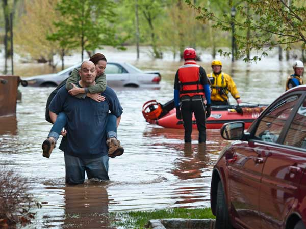 Rene Rivera carries his wife, Melissa Hotsko, from their building at the Riverview Landing Apartments in Eagleville, West Norriton after the Schuylkill River flooded the building´s garage and first-floor units. He decided not to wait for rescue boats to arrive. ( RON TARVER / Staff Photographer ) MAY 1 2014
