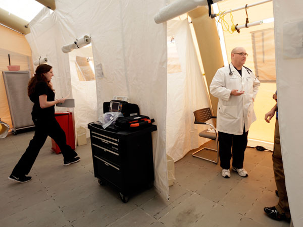 Registered nurse Michelle Newbury, left, and physician assistant Scott Fillman meet with patients in a tent set up for a people with flu symptoms, just outside the emergency entrance at the Lehigh Valley Hospital last January. (AP Photo/Matt Rourke)