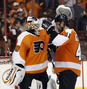 Goalie Ilya Bryzgalov and defenseman Andrej Meszaros celebrate the Flyers´ win in the team´s home opener on Wednesday night. (YONG KIM / Staff Photographer)