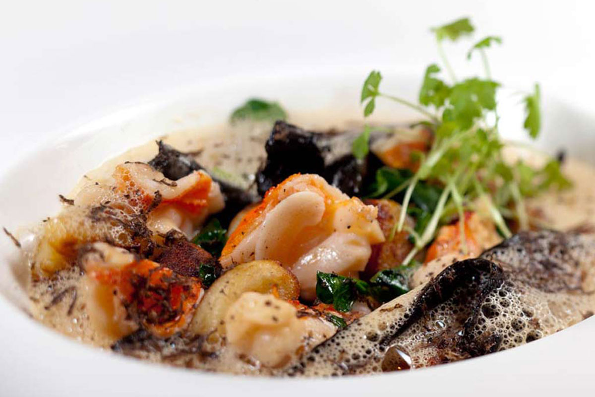 Lobster and gnocchi, with black trumpet mushrooms, pea leaves, sauce American, black truffle, as served at Fond.