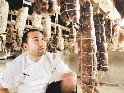 Chef Joe Cicala in Le Virtu´s cellar curing room, amid a forest of salumi. (DAVID M WARREN / Staff Photographer)