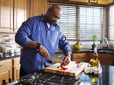 "Gonna be spicy: In Big Daddy's television kitchen, Aaron McCargo Jr. slices jalapeños for a Season 5 segment of the Food Network's ""Big Daddy´s House."""