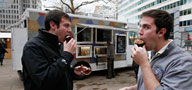 Andy Campbell (left) and Brian Wing (right) eat cupcakes purchased from the Cupcake Truck.