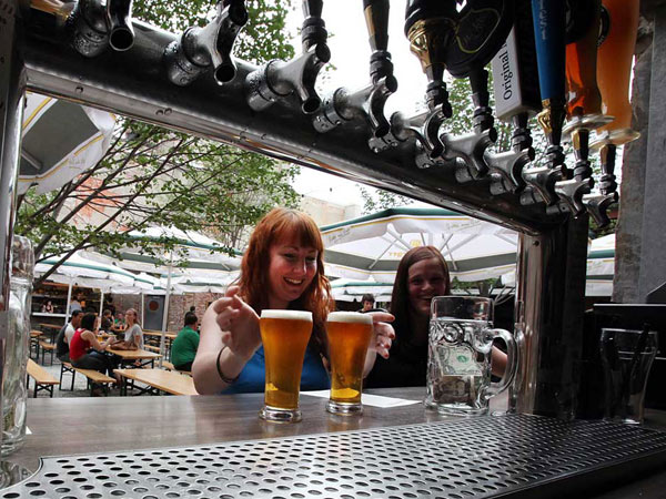 Alison Neff, 33 grabs her beer at Frankford Hall in Fishtown. (Steven M. Falk / Staff Photographer )