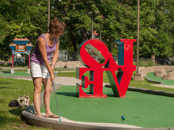 Melissa Robischaw of Albany, New York putts at Franklin Square Mini-Golf in Philadelphia. The course features a number of miniature Philadelphia landmarks. July 8, 2014, Philadelphia, Pennsylvania. ( MATTHEW HALL / Staff Photographer )