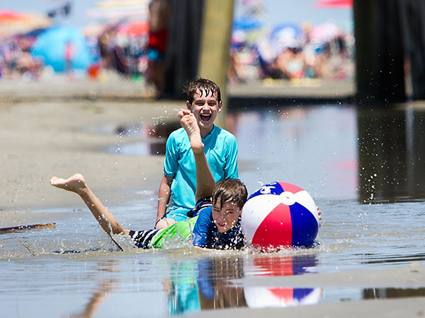 9-year-old Joseph Richard lands with a splash while chasing a beach ball punched by his friend 10-year-old Matthew Sasso (behind) while playing on the beach in Avalon, June 29, 2014.  ( DAVID M WARREN / Staff Photographer )