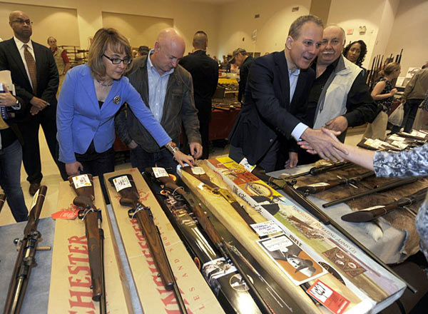 This 2013 file photo shows former Arizona Rep. Gabby Giffords, her husband Mark Kelly, center, and New York Attorney General Eric Schneiderman, touring the New EastCoast Arms Collectors Associates arms fair in Saratoga Springs, N.Y. A divided Congress denied President Barack Obama´s calls for reforms. The federal gun lobby, led by the National Rifle Association, is arguably stronger than ever. And polls suggest that support for new gun laws is slipping as the memory of Newtown´s horror fades. (AP Photo/Tim Roske, File, Pool)