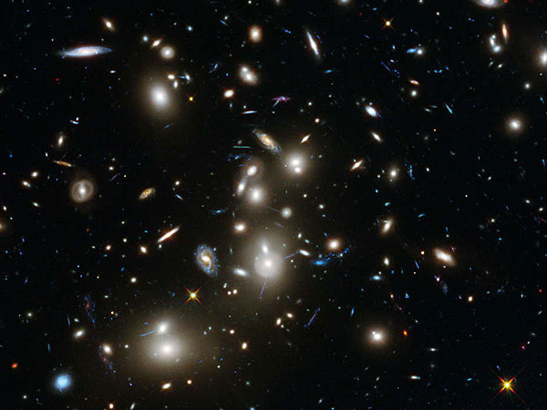A view of galaxies in the Abell 2744 cluster, and blue galaxies behind it, distorted and amplified by gravitational lensing. The long-exposure image shows some of the intrinsically faintest and youngest galaxies ever detected in visible light.