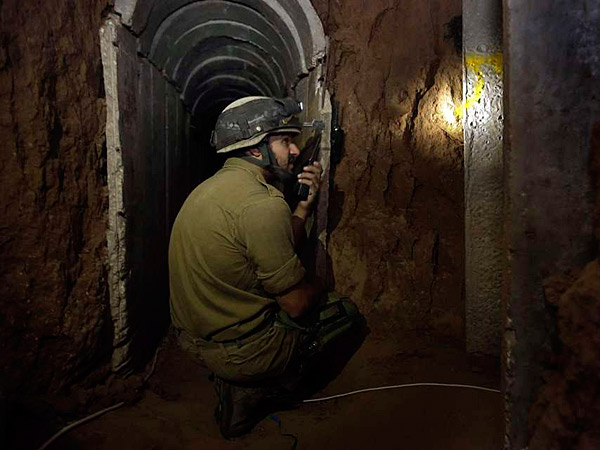 "An Israeli soldier kneels inside a tunnel discovered near the border with the Gaza Strip. ""The tunnel is extremely advanced,"" Brig. Gen. Mickey Edelstein told reporters. (AP)"