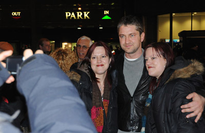 Gerard Butler poses with two fans. (Photo: HUGHE DILLON)