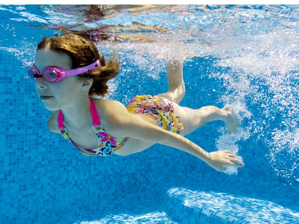 A young girl swims under water.