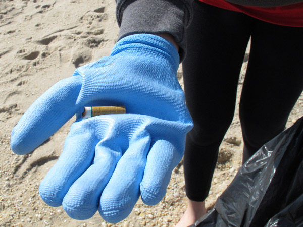 "Cigarette butts alone accounted for about 50,000 of the 350,000 bits of trash pulled from N.J. beaches in two ""sweeps"" last year.  The blue glove belongs to Melissa Shapero, helping with the cleanup in April 2012 at Point Pleasant Beach. (Photo by Wayne Parry / Associated Press)"