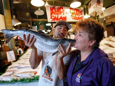 Vendor Taho Kakutania, left, playfully encourages tourist Anne Moral, of Tucson, Ariz., to kiss a coho salmon at the Pike Place Fish Market Monday, Sept. 20, 2010, in Seattle. U.S. government food regulators pondered Monday whether to say, for the first time, that it´s OK to market a genetically engineered animal as safe for American people to eat. The Food and Drug Administration is holding two days of hearings on a request to market genetically modified salmon. (AP Photo/Elaine Thompson)