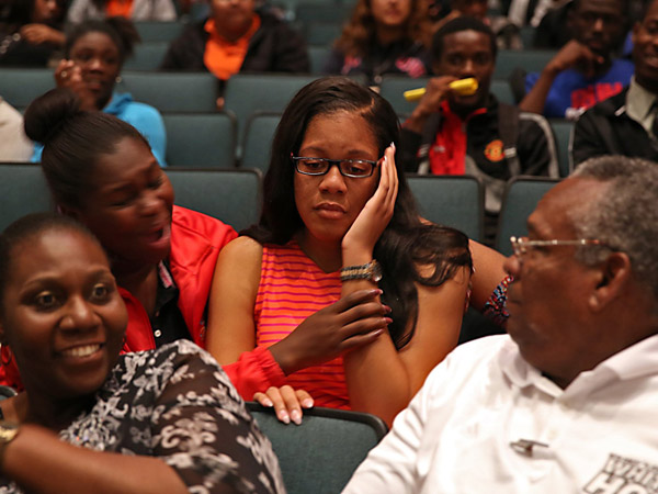 Ashley Milfort, center, a senior at Booker T. Washington High, is stunned as a four-year, college scholarship is announced by the Biscayne Bay Kiwanis Club at a surprise ceremony, May 6, 2014. (Walter Michot/Miami Herald/MCT)