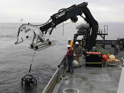 The Eye-in-the-Sea video camera, which weighs 502 pounds, is lowered into the Pacific Ocean off the California coast. (Eric Risberg / AP)
