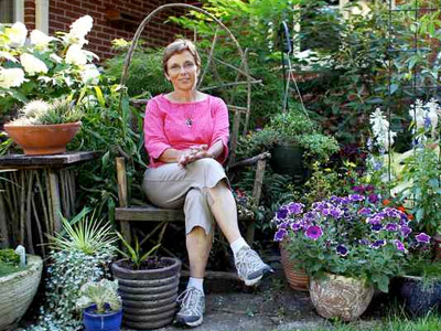 "Janice Becker sits among the many flowers in her backyard garden in Deerfield, Ill. Becker calls herself a ""plant geek"" because of the number and variety of plants she has. (Chris Sweda / Chicago Tribune)"