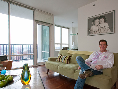 Mike Jerrick lounges in his living room, with a commanding view of the city and a photograph of his daughters (who are no in their 30s). (Akira Suwa / Staff Photographer)