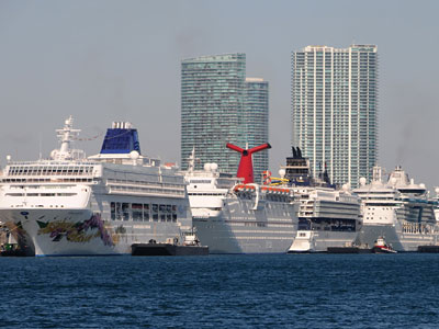 In this Monday, March 15, 2010 photo, five cruise ships are lined up at the Port of Miami, in Miami. A few miles away, at the Miami Beach Convention Center. (AP Photo/Cruise Shipping Miami, Andy Newman)