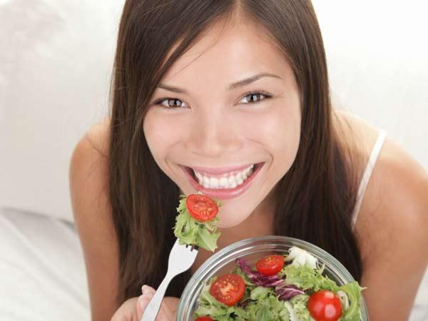 Woman eating a salad she prepared.