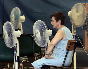 A woman tries to cool off during a weeklong heat wave in downtown Milan, Italy, 2005. (Luca Bruno/AP)