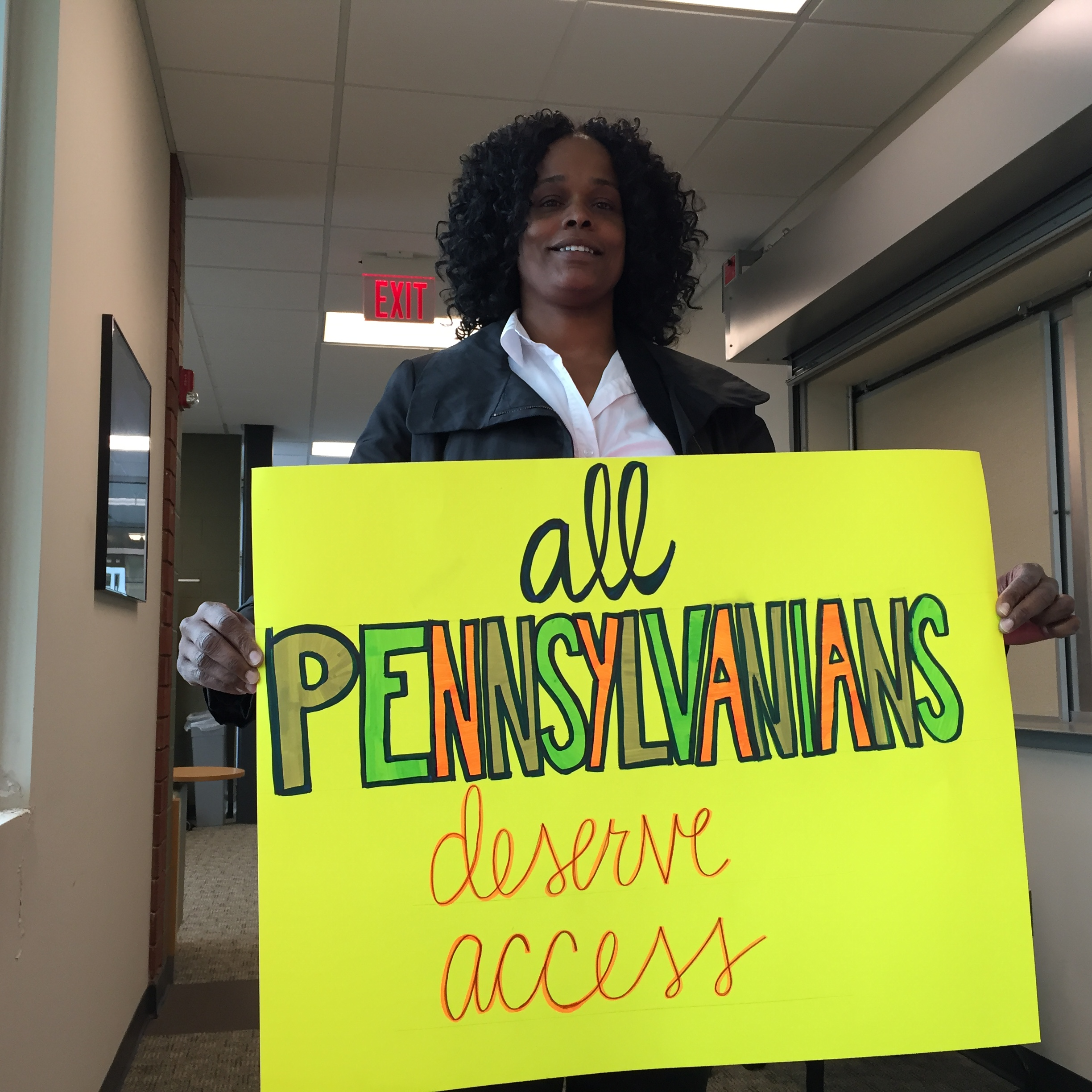 """Tawanda Preston, a patient navigator at a Drexel University infectious diseases clinic, holds a sign saying """"All Pennsylvanians Deserve Access"""" during a state advisory committee discussion in May 2016 in Mechanicsburg, Pa., about Medicaid guidelines that restrict coverage for expensive drugs that can effectively cure hepatitis C. The panel recommended coverage but the state has not announced a decision."""