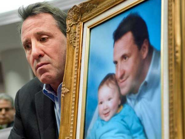 Neil Heslin holds a portrait of himself and his son, Jesse Lewis, who was killed in the Newtown massacre. AP Photo/Jessica Hill