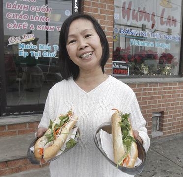 Owner, Tam Le, owner of Cafe Huong Lan on South Eighth Street, holds two Vietnamese pork hoagies.