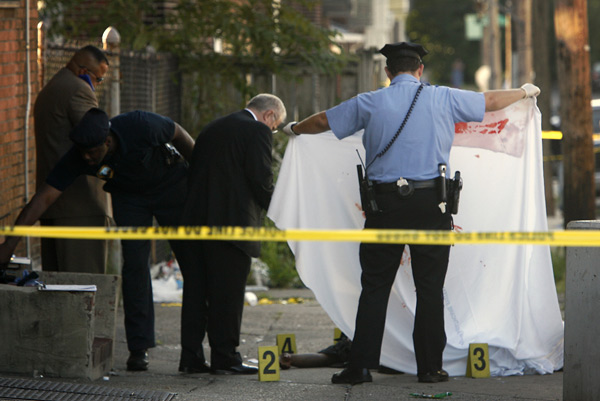 Police look at the body of a young man dead at 66th Street near Woodland Avenue in Southwest Philadelphia on Sept. 2, 2009.