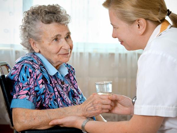 Nurse checking on elderly woman.