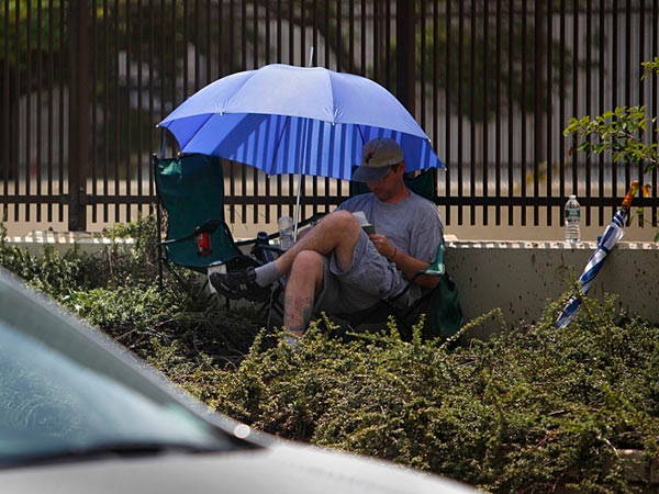 July 2013 file photo: Zac Linert sits along Vine Street enjoying a book in the summer sun. Linert, who was looking for employment, took some time to rest from the heat and relax. (LUKE RAFFERTY/Staff Photographer)