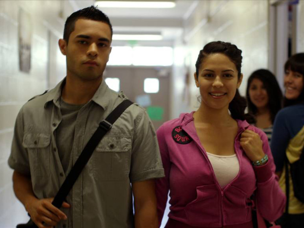 "Janine Larina as Jessie Martinez and  Gabriel Chavarria as Jacob Aguilar walk through a hallway on ""East Los High."""